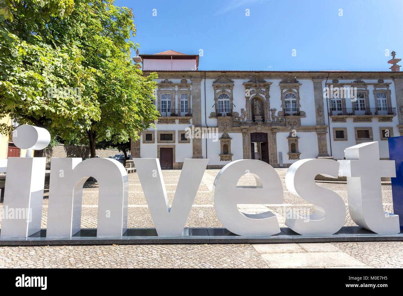 Word Invest created by big plastic letters in front of traditional architecture - Stock Image