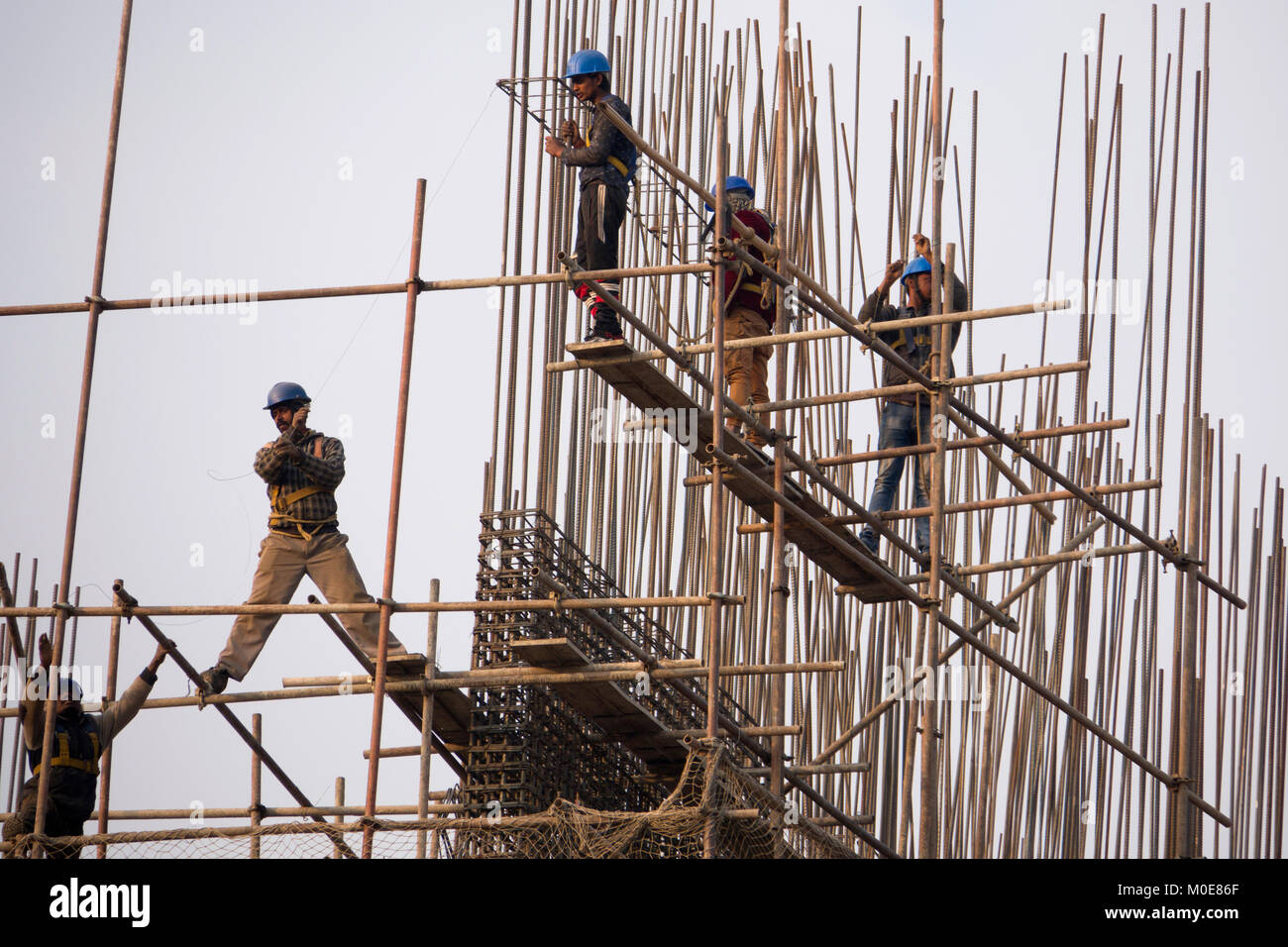 Construction workers securing steel on high rise building project in Kathmandu, Nepal - Stock Image