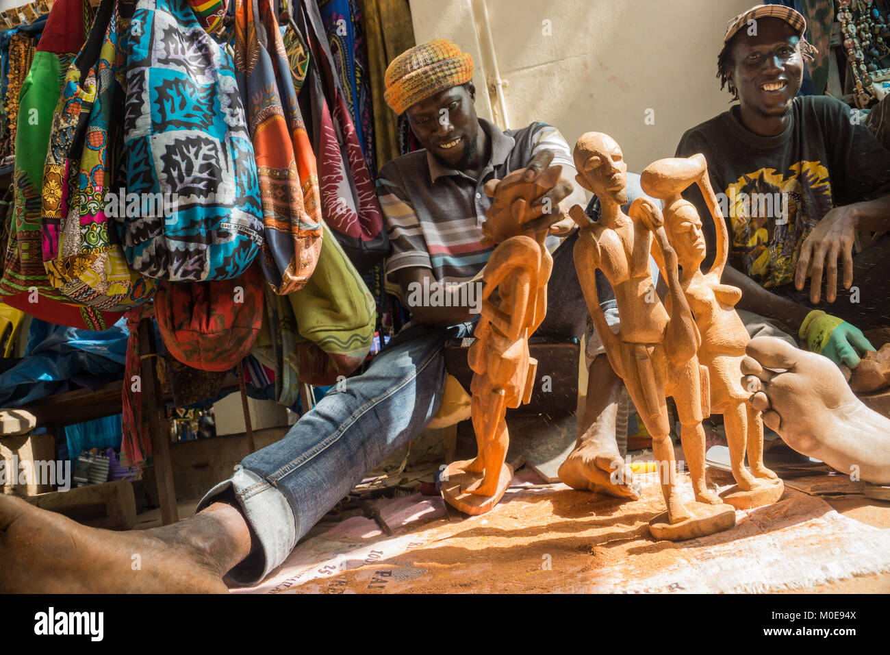 An African man carves wooden statues in Senegambia, Gambia - Stock Image