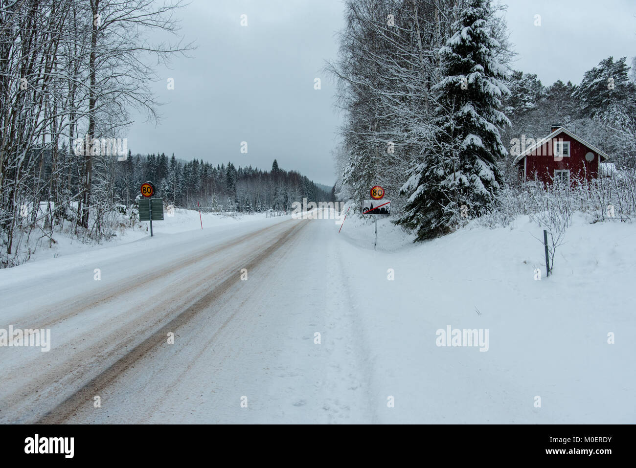 traffic sign with 80 kilometer per hour and a red wooden house in Varmland Sweden - Stock Image