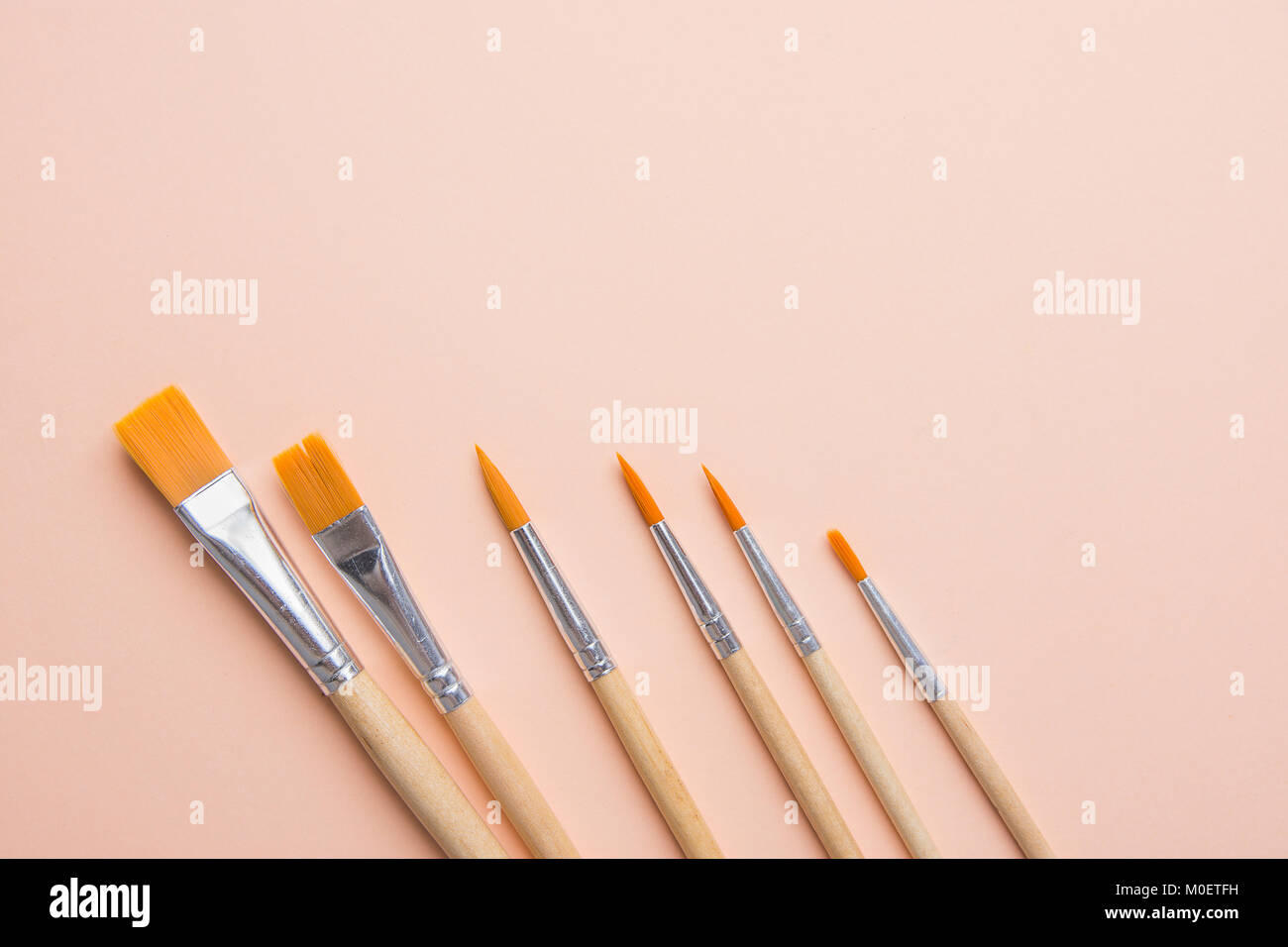 Bunch Of Various Kinds Of Paint Brushes On Light Pink Peachy Stock