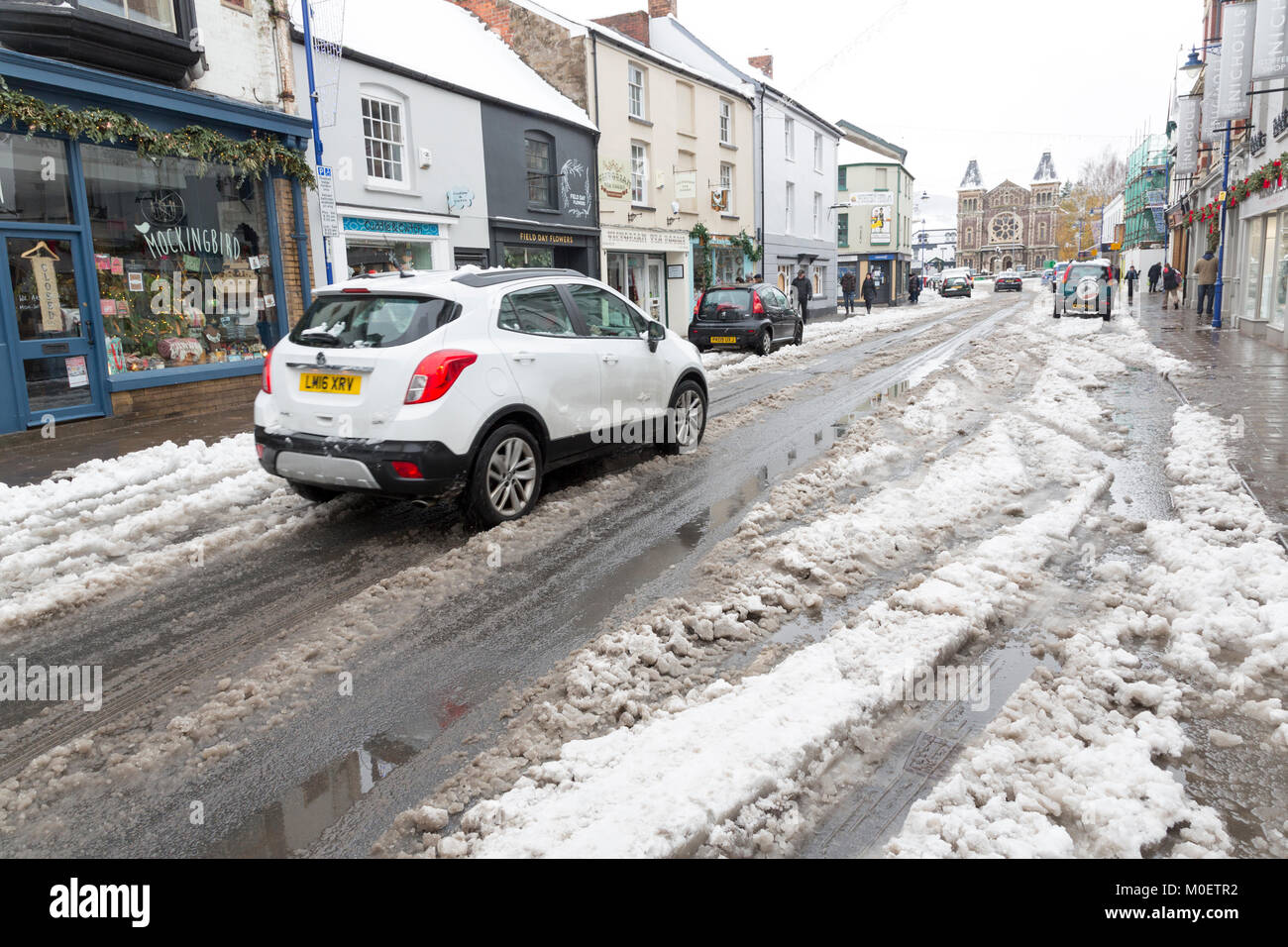 Cars driving through slush in street, Abergavenny, Wales, UK - Stock Image