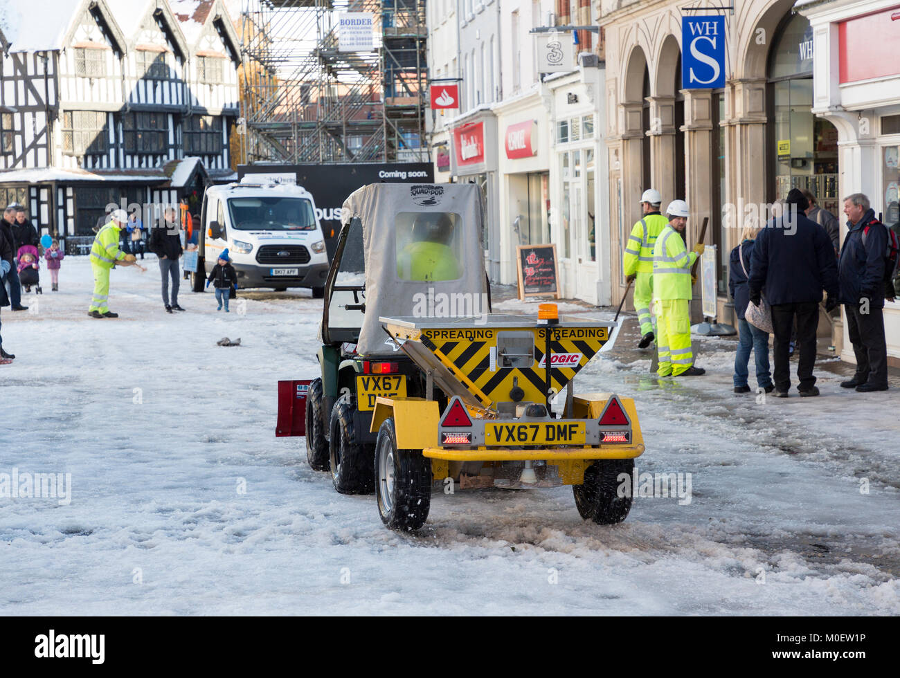 Mini slat spreader and workmen clearing snow from shopping centre street, Hereford, UK - Stock Image
