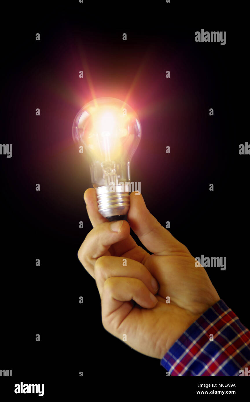 Classic bulb glowing in hand - new idea concept. Shine and light around glass lightbulb. - Stock Image