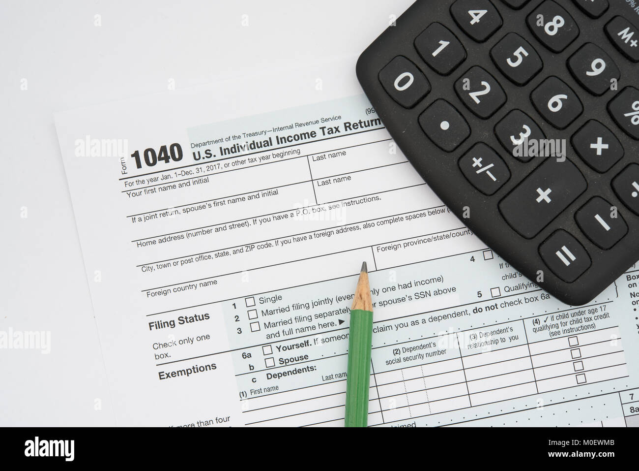US Federal income tax form 1040 for individuals, with a pencil and a calculator. - Stock Image