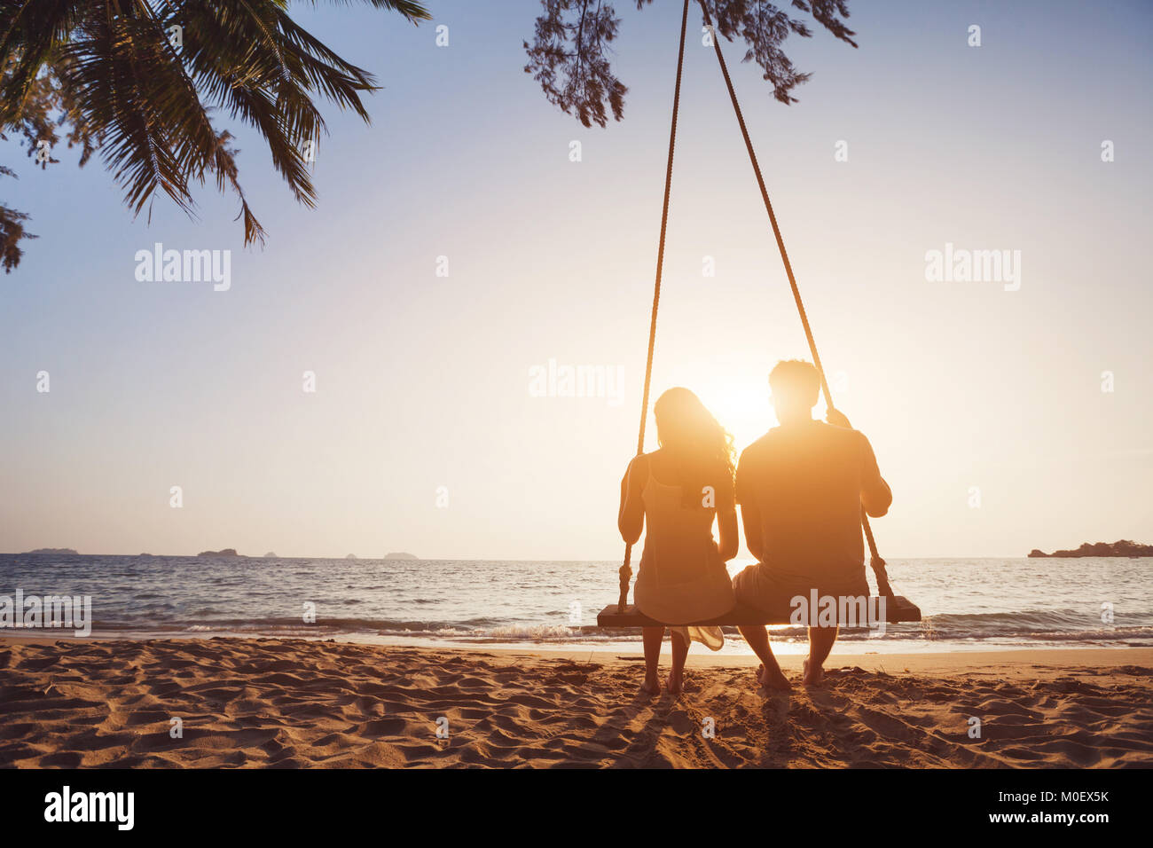 romantic couple in love sitting together on rope swing at sunset beach, silhouettes of young man and woman on holidays - Stock Image