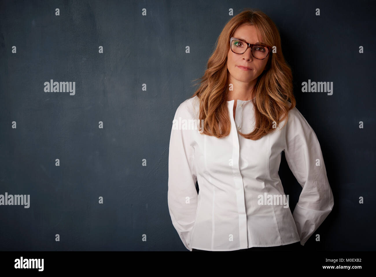 Studio portrait of a beautiful smiling mature woman wearing eyewear and white shirt while standing at dark background. - Stock Image