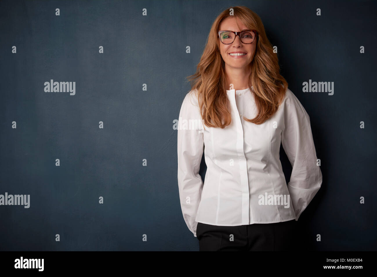 Studio portrait of a laughing beautiful mature woman wearing eyewear and white shirt while standing at dark background. - Stock Image