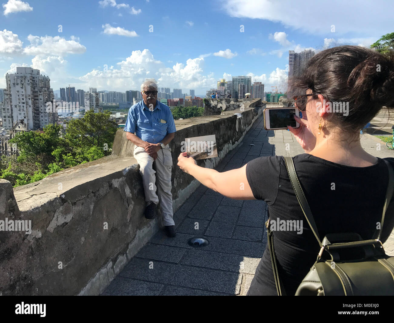 Woman holding an old photo photographing her father in same place years later, Macau, China - Stock Image