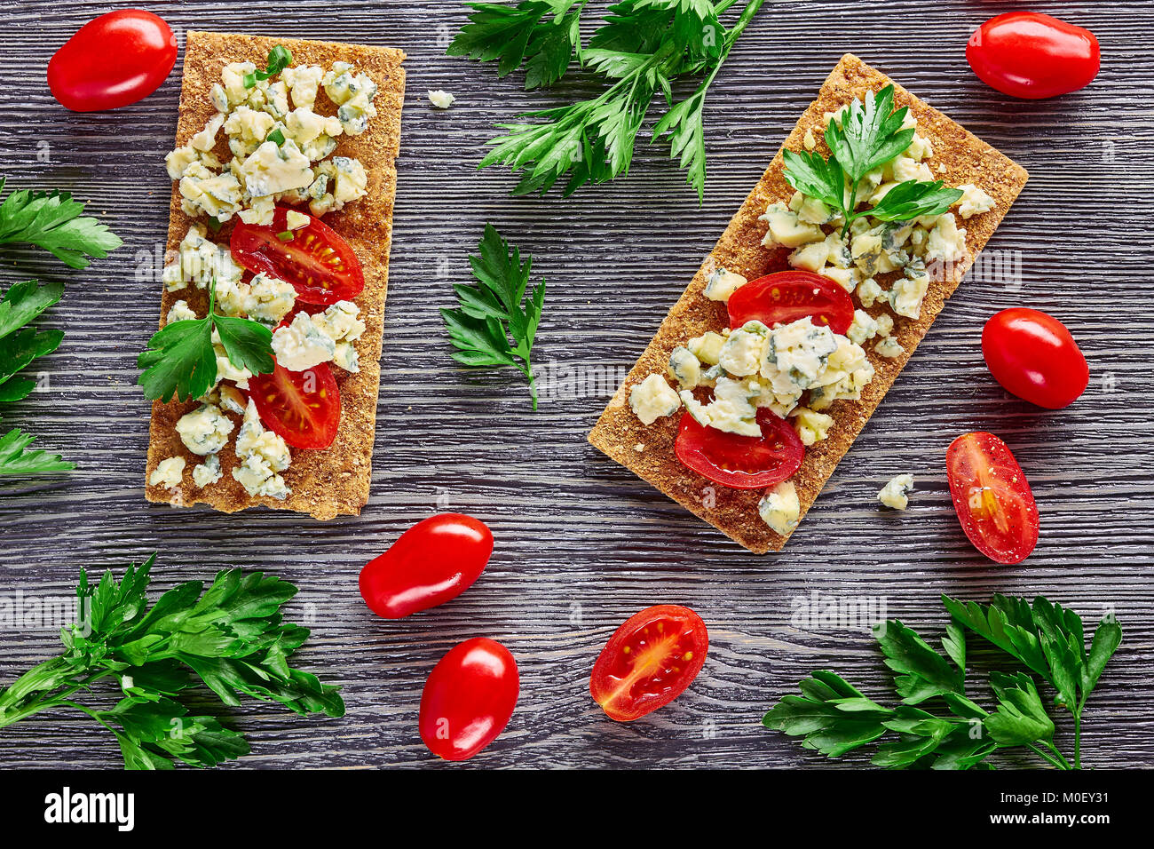 Crispbread with blue cheese and tomatoes - Stock Image