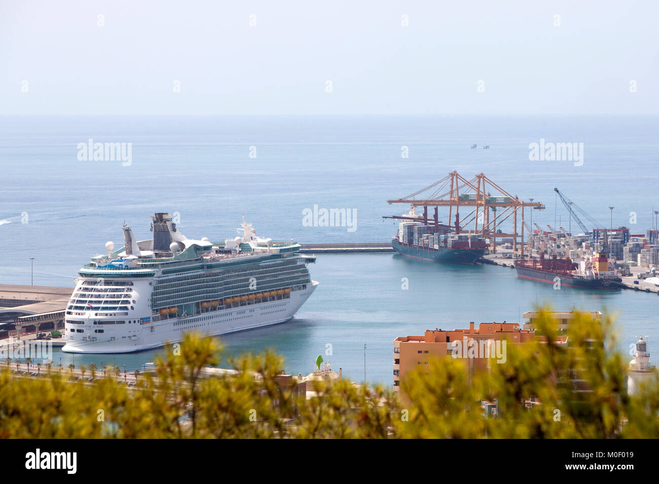 Royal Caribbean Navigator of the seas cruise ship berthed in Malaga Spain alongside two bulk carrier ships in summer - Stock Image