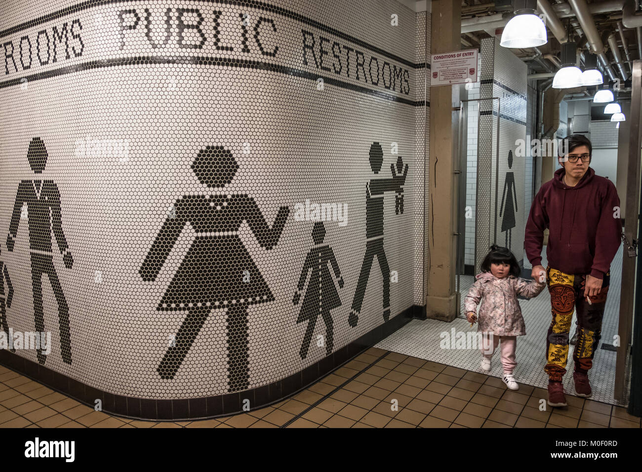 father exiting public restrooms with daughter, Seattle, Washington, USA - Stock Image