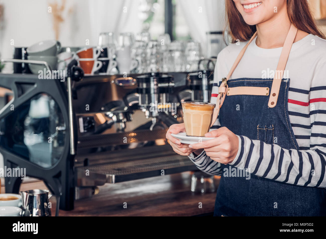 asia woman barista wear jean apron holding hot coffee cup served to customer with smiling face at bar counter,Cafe - Stock Image