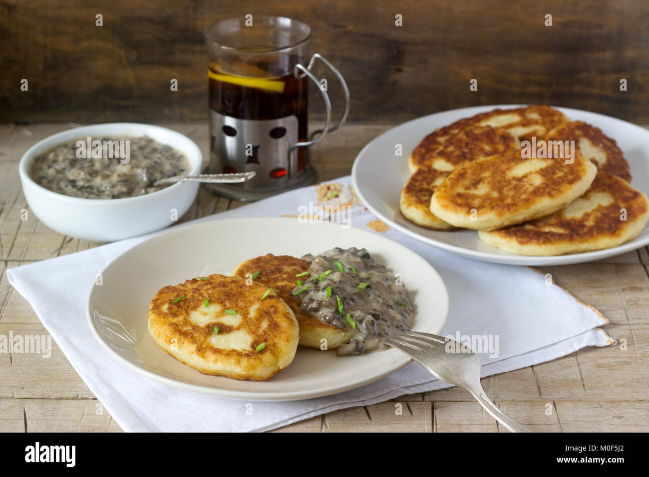 Potato cutlets or pancakes with mushroom sauce and green onions. Rustic style. - Stock Image