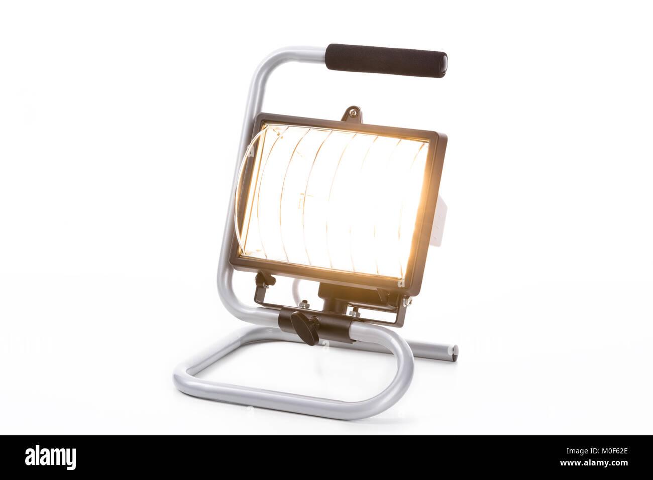 Construction light isolated on white background, closeup, with burning halogen light - Stock Image
