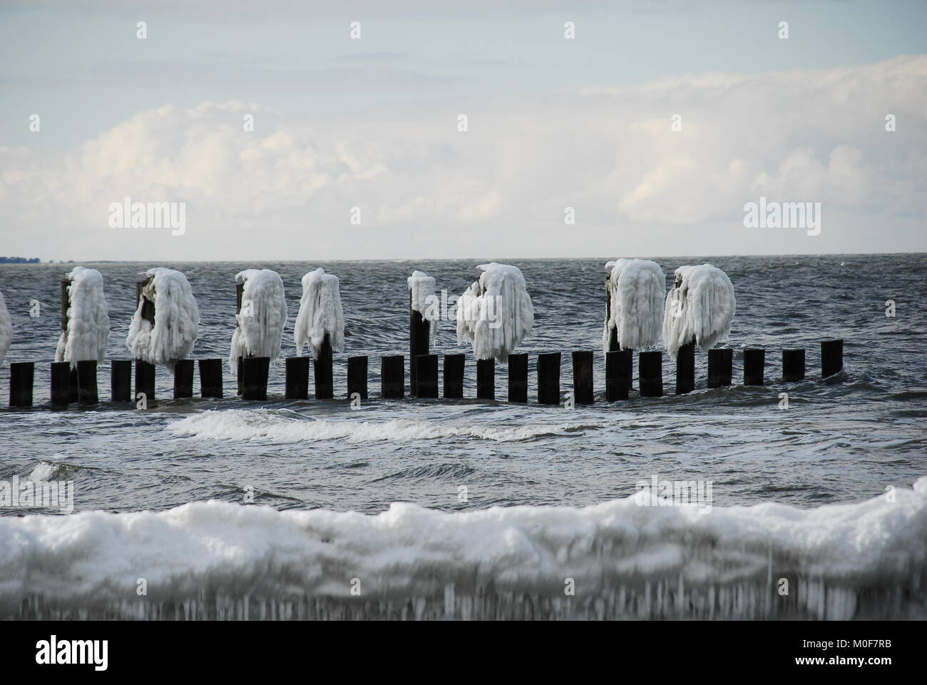 Accumulation of ice on groynes in front of a magnificent cloud background - Stock Image
