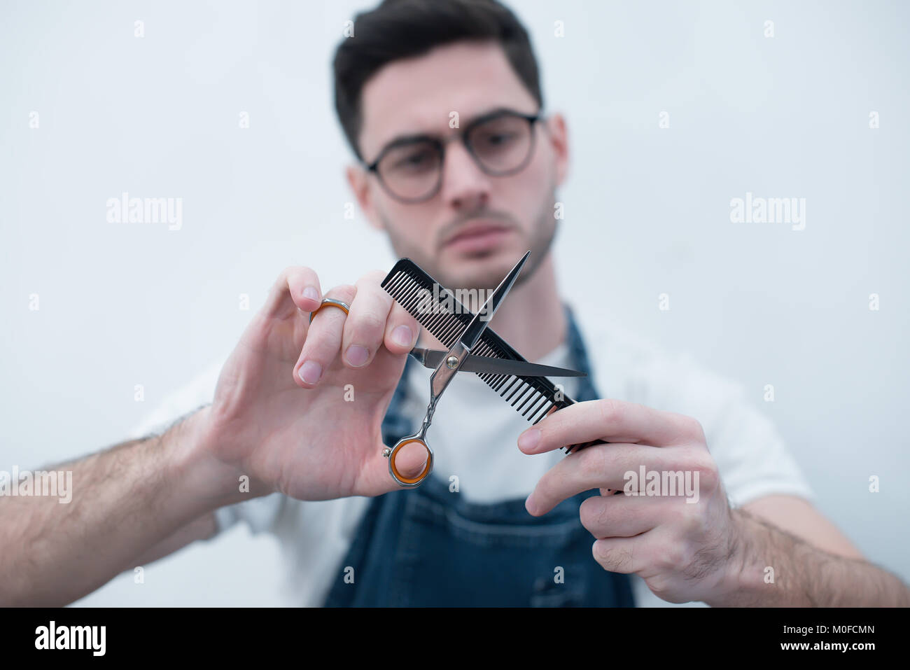 Barber holds the comb and scissors on his arms outstretched against the background of a white wall. Focus on tools. - Stock Image