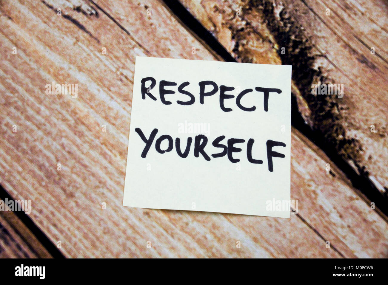 Respect Yourself -Hand written yellow sticky note wooden background - Stock Image