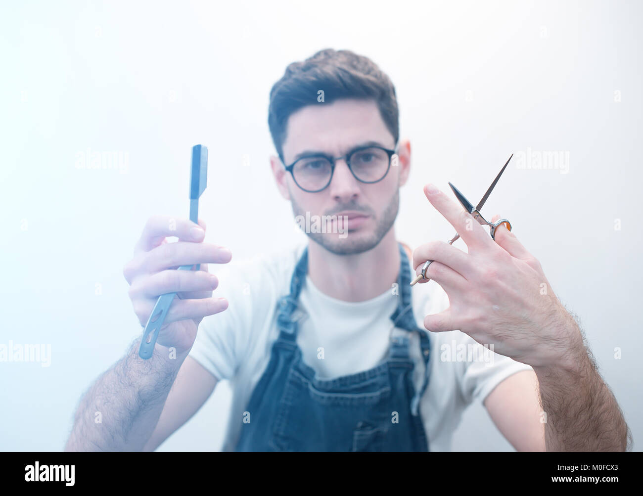 Barber keeps scissors and a razor against the background of a white wall. Focus on tools. - Stock Image