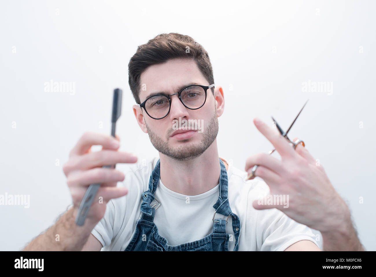 Barber keeps scissors and a razor against the background of a white wall. - Stock Image