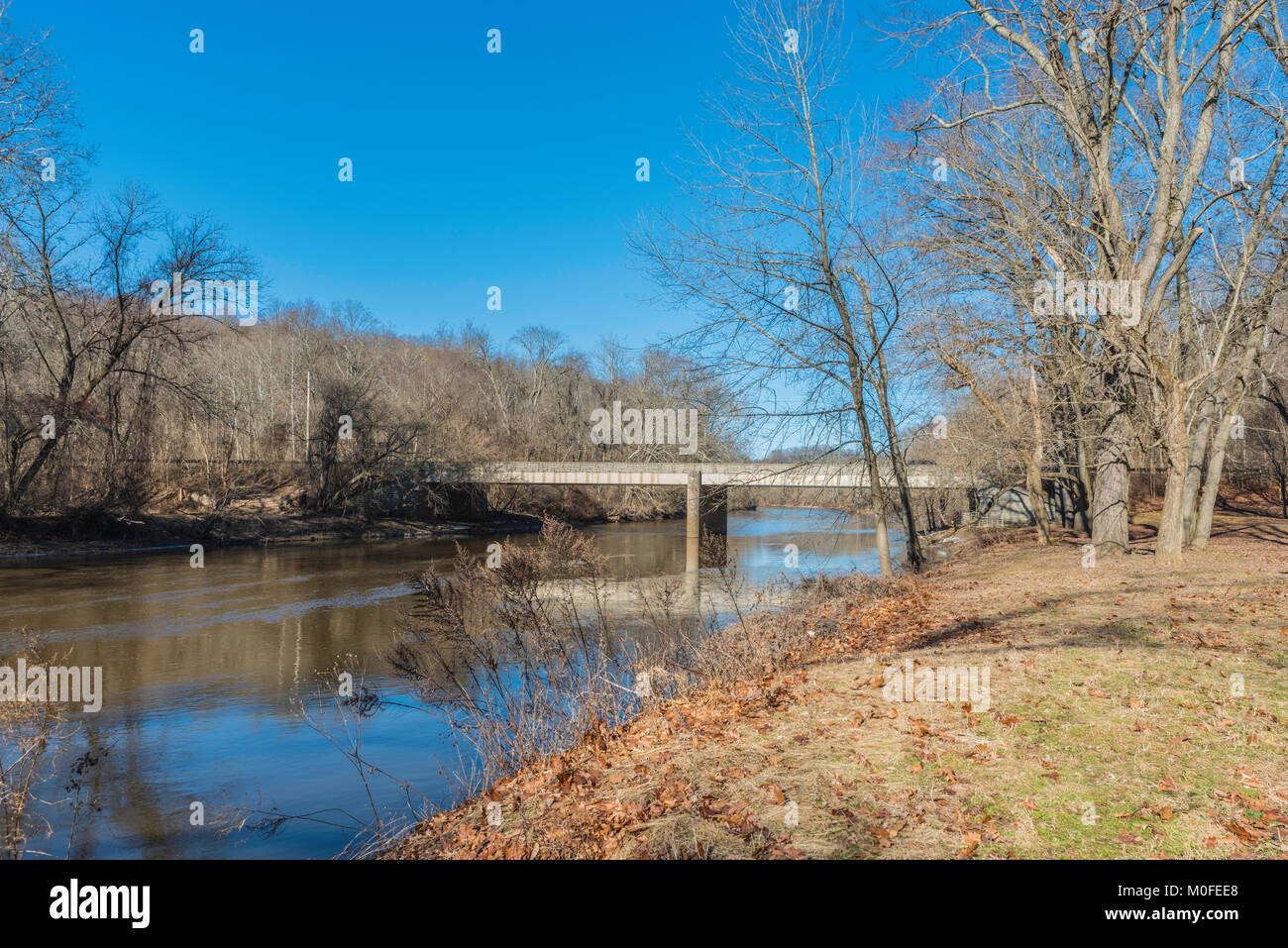 Brandywine Creek in Wilmington, Delaware with a bright blue sky and reflections in the water looking toward Thompsons - Stock Image