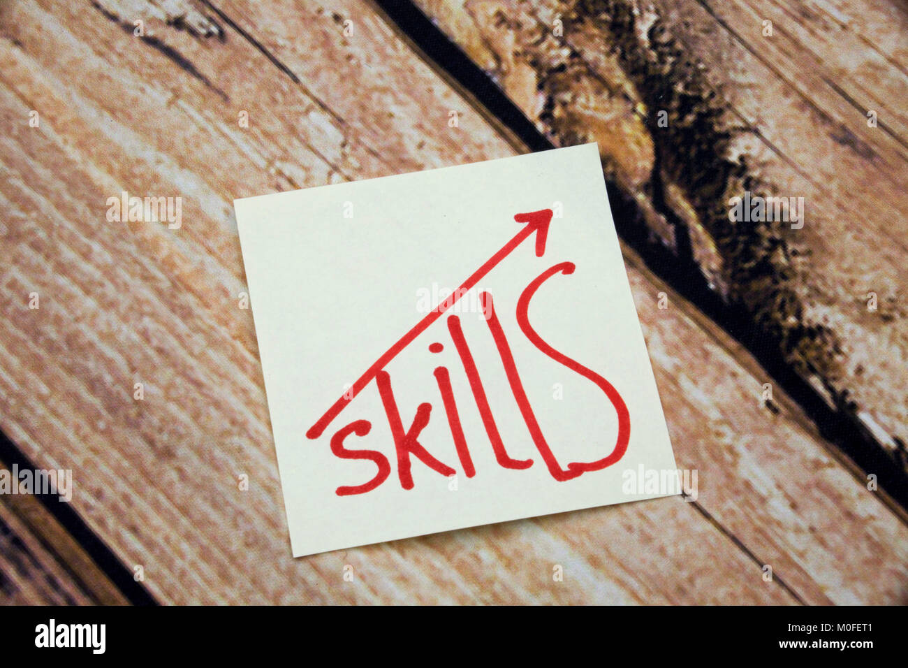 Skills written on sticky note on the wooden table Improve Your skills Concept - Stock Image