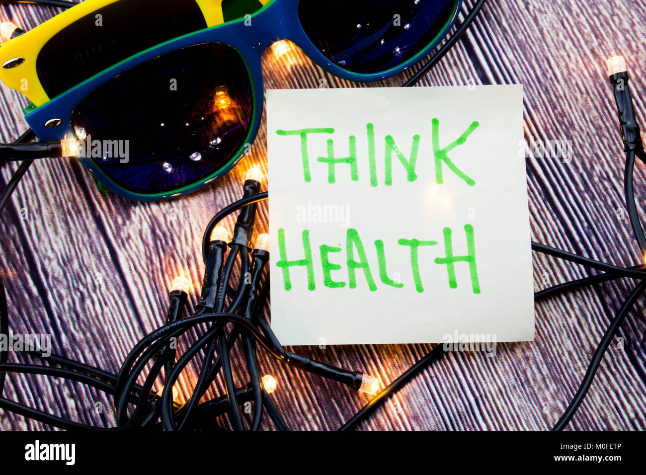 Think Health Sticky note paper with sunglasses on a wooden background with lights concept for health awareness - Stock Image