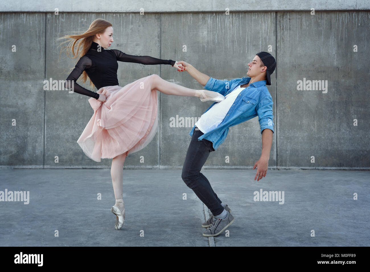 A young couple in love passionately dances on a city street. Ballerina and athlete parkour. Meshenie classical and Stock Photo