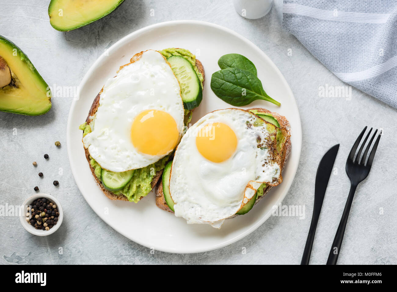 Egg and avocado breakfast toast on white plate. Table top view. Healthy eating dieting concept Stock Photo