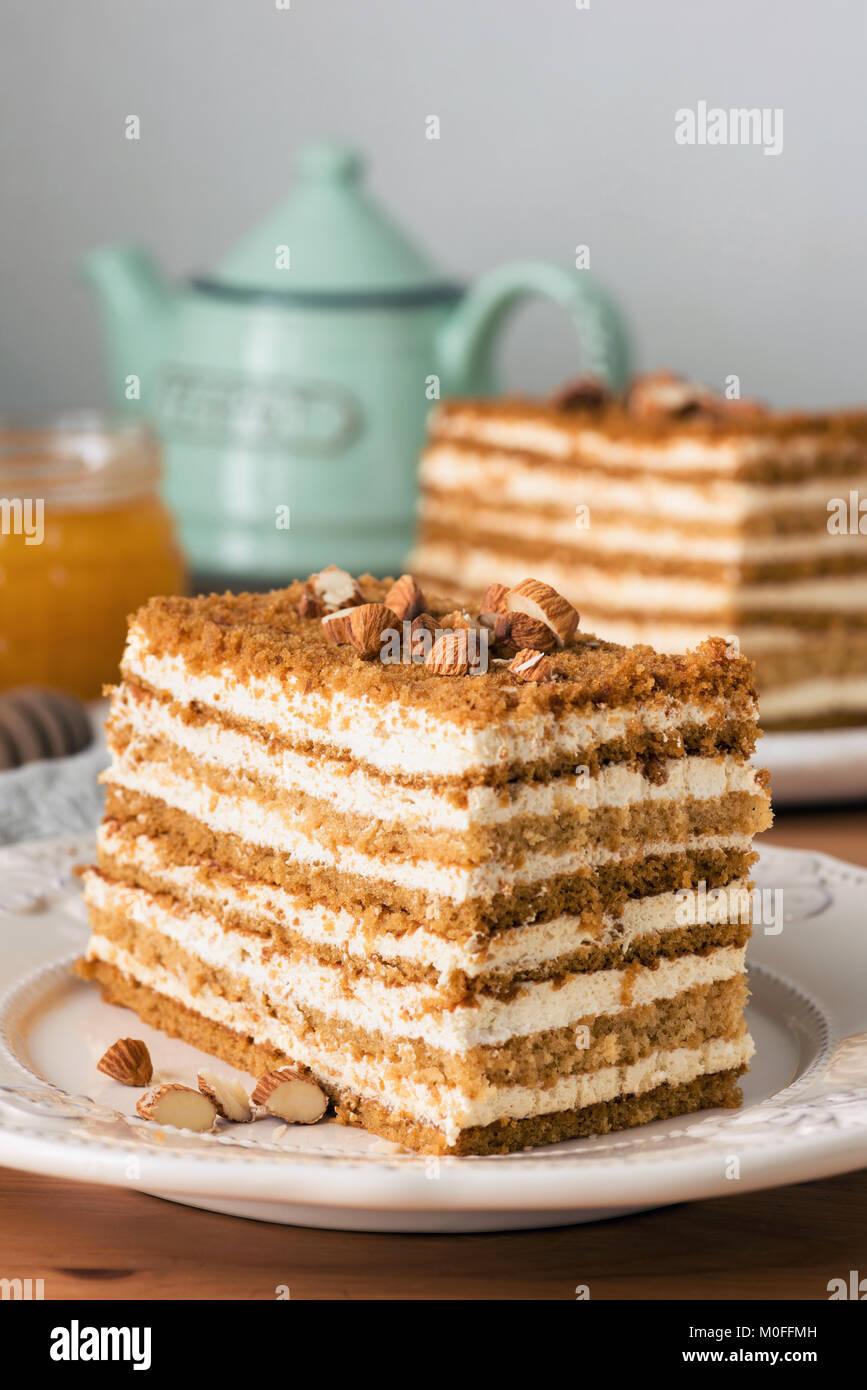 Honey cake Medovik on white plate. Closeup view, toned image - Stock Image