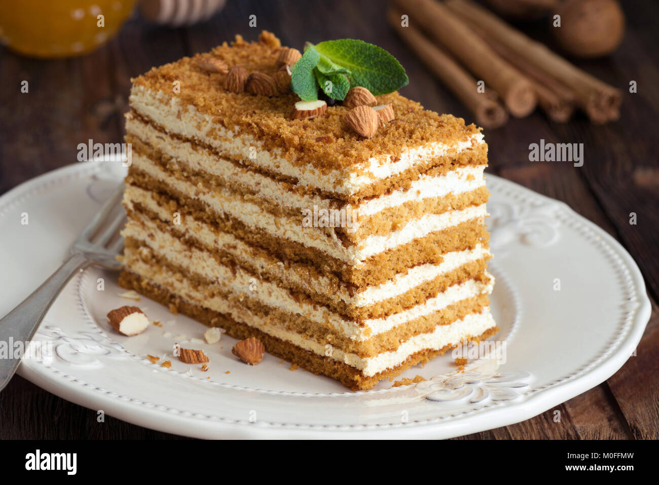 Honey layer cake Medovik decorated with mint leaf and almonds. Russian honey cake. Closeup view - Stock Image