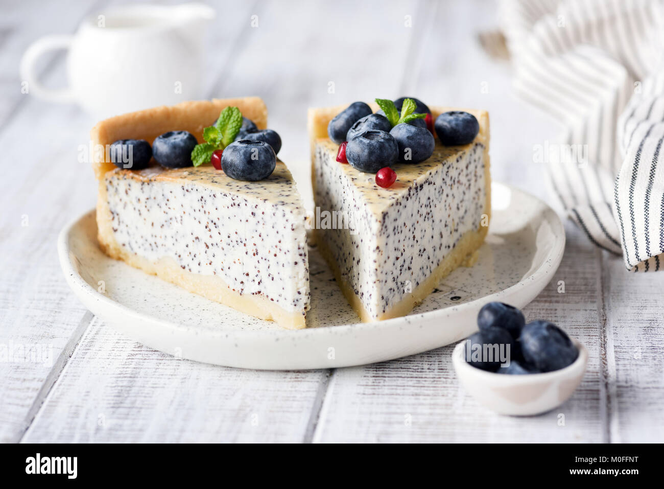 Cheesecake with poppy and blueberries. Homemade poppy pie on white plate decorated with blueberries and mint. Closeup - Stock Image