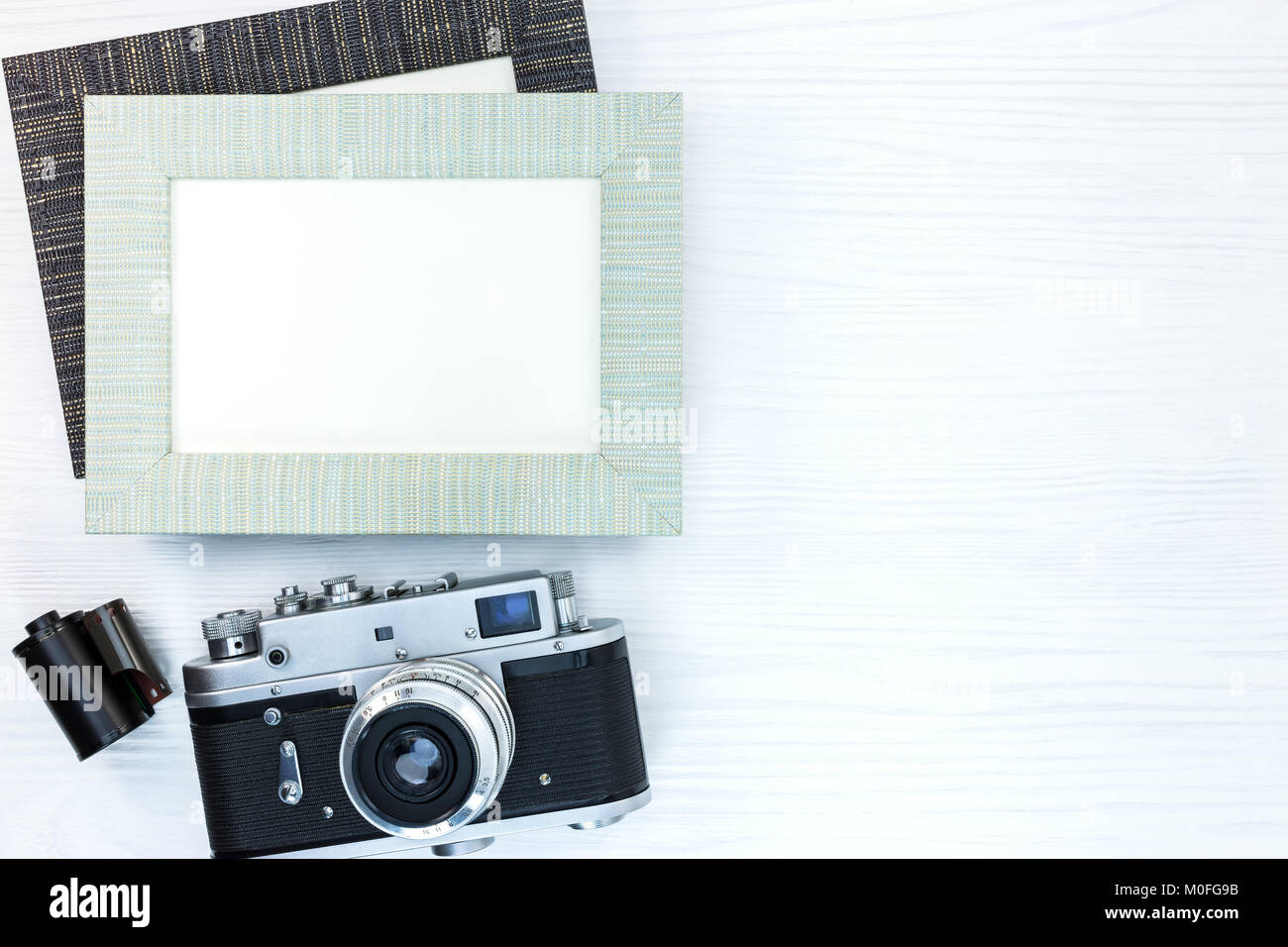 retro camera with film roll and two empty photo frames on white ...
