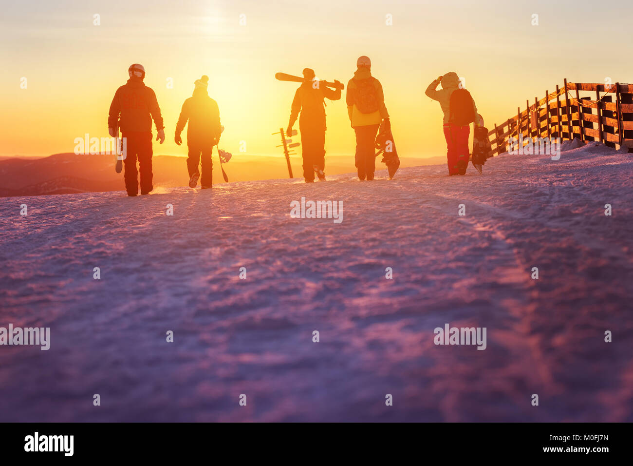 Friends with ski and snowboards walking to sunset - Stock Image