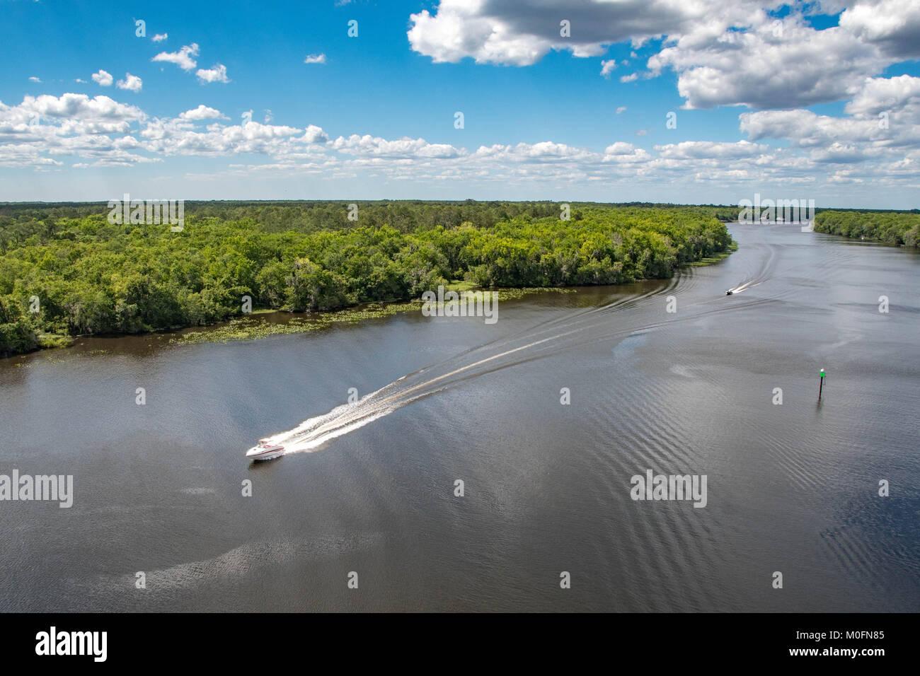 Boats swiftly glide across river in marshlands of Florida coastline - Stock Image