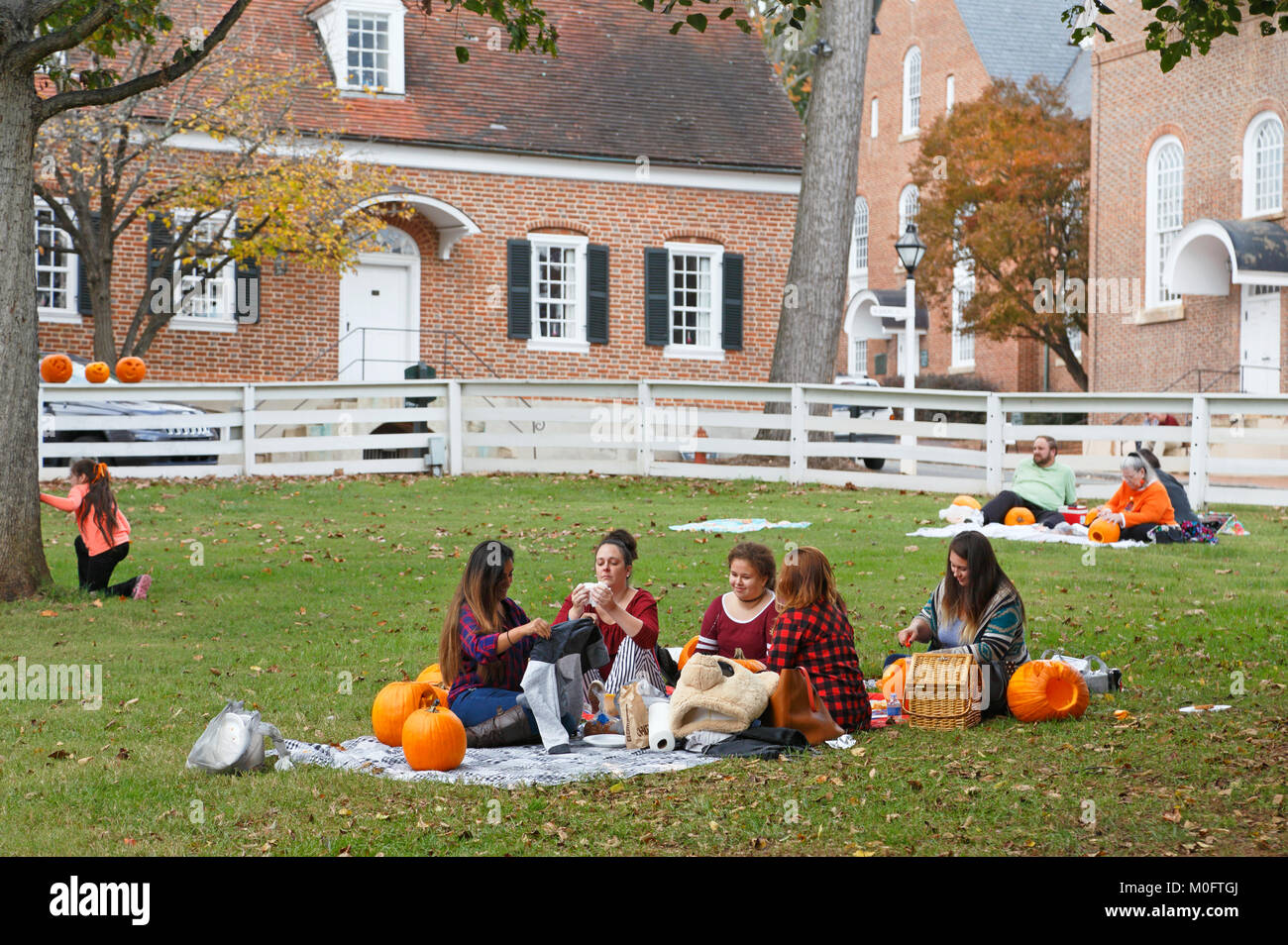 People having picnic and carving pumpkins at the yearly pumpkin carving event in Old Salem Stock Photo
