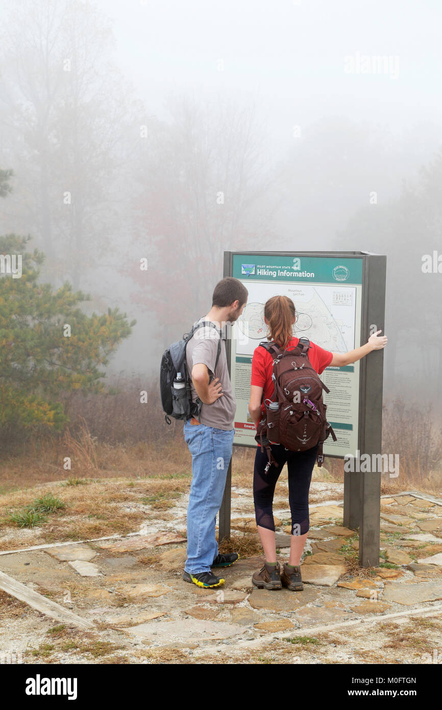 Hikers looking at trail map, Pilot Mountain, North Carolina. Stock Photo