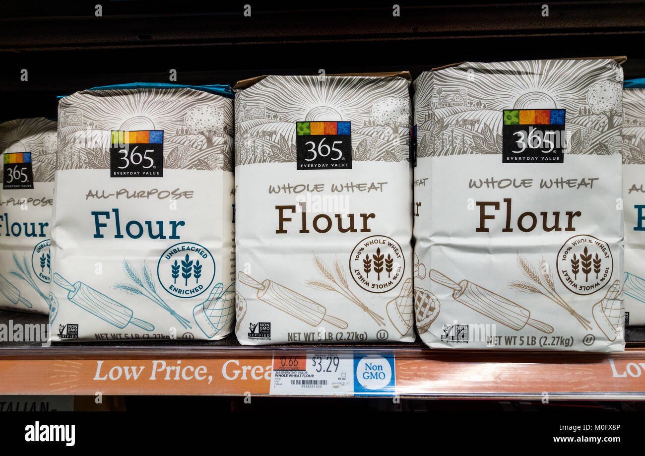 Bags of white and whole wheat flour on a shelf at Whole Foods Market - Stock Image