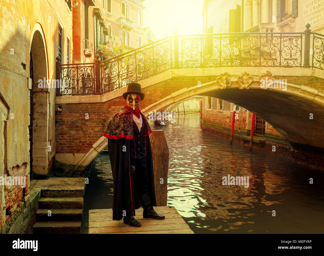 Unidentified man in black costume, hat and mask posing in front of small Venetian bridge over narrow canal during Stock Photo