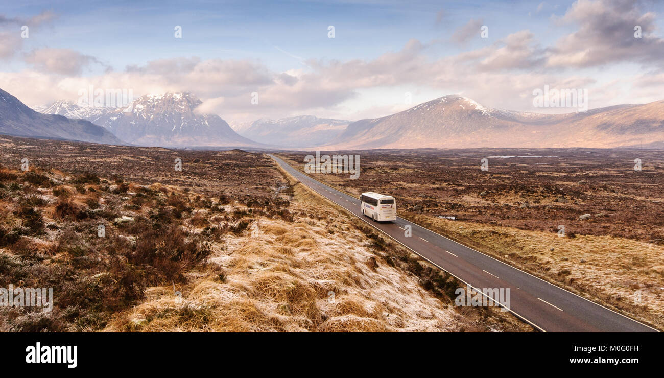 Glen Coe, Scotland, UK - January 16, 2012: A tourist coach travels along the A82 main road in the vast and bleak - Stock Image