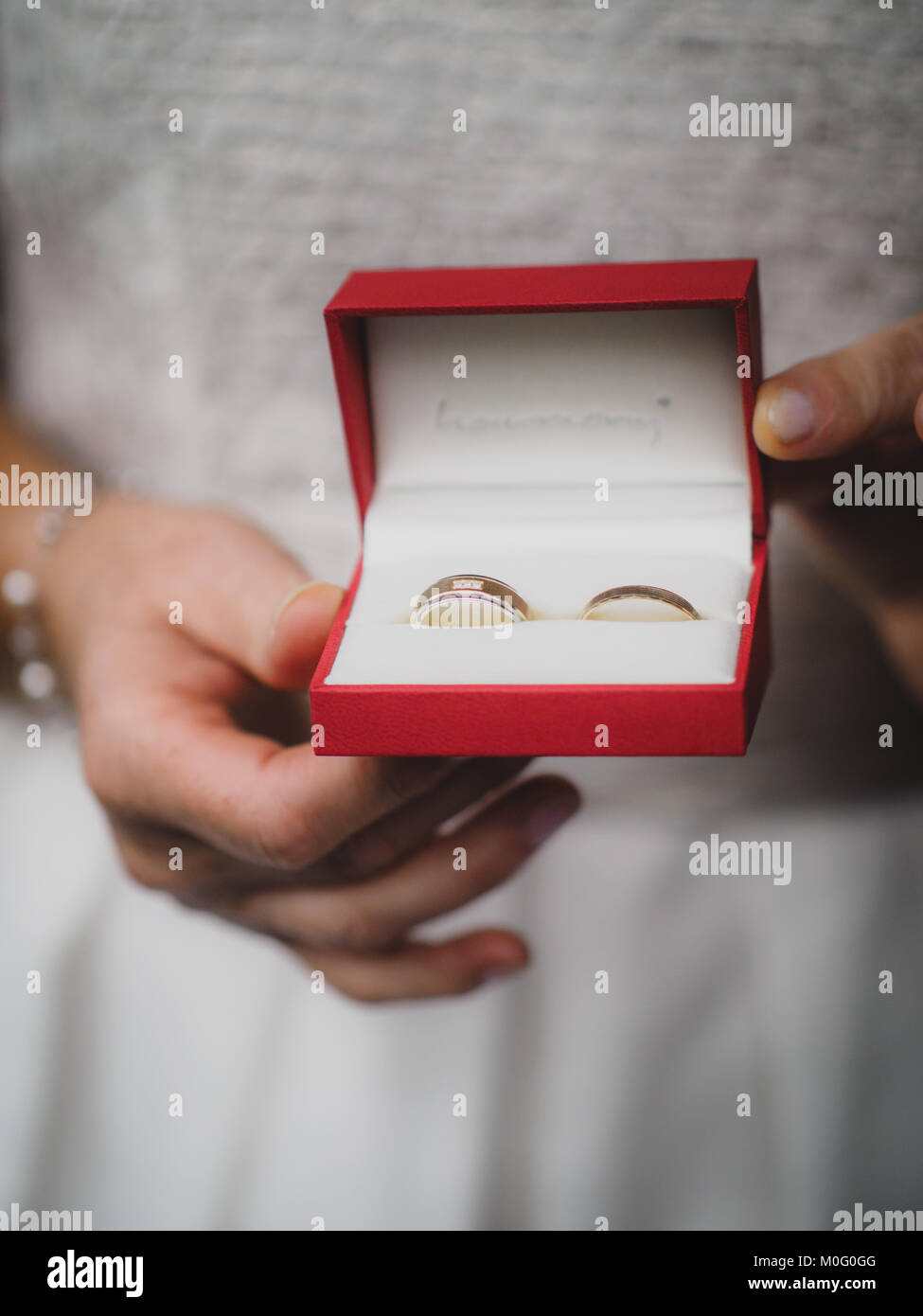 The bride holds her wedding ring in the camera - Stock Image