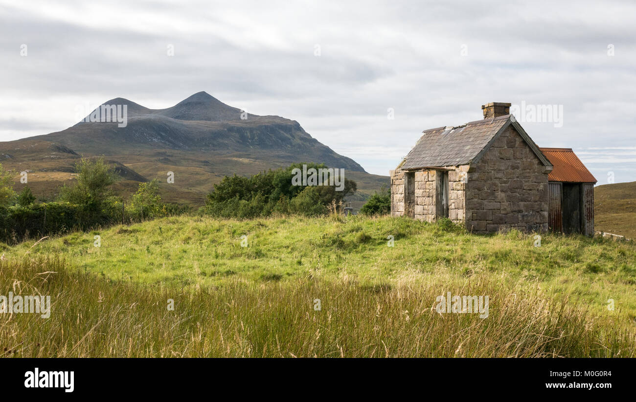 Cul Mor mountain rises behind a barn in the remote village of Elphin in Assynt in the Northwest Highlands of Scotland. - Stock Image