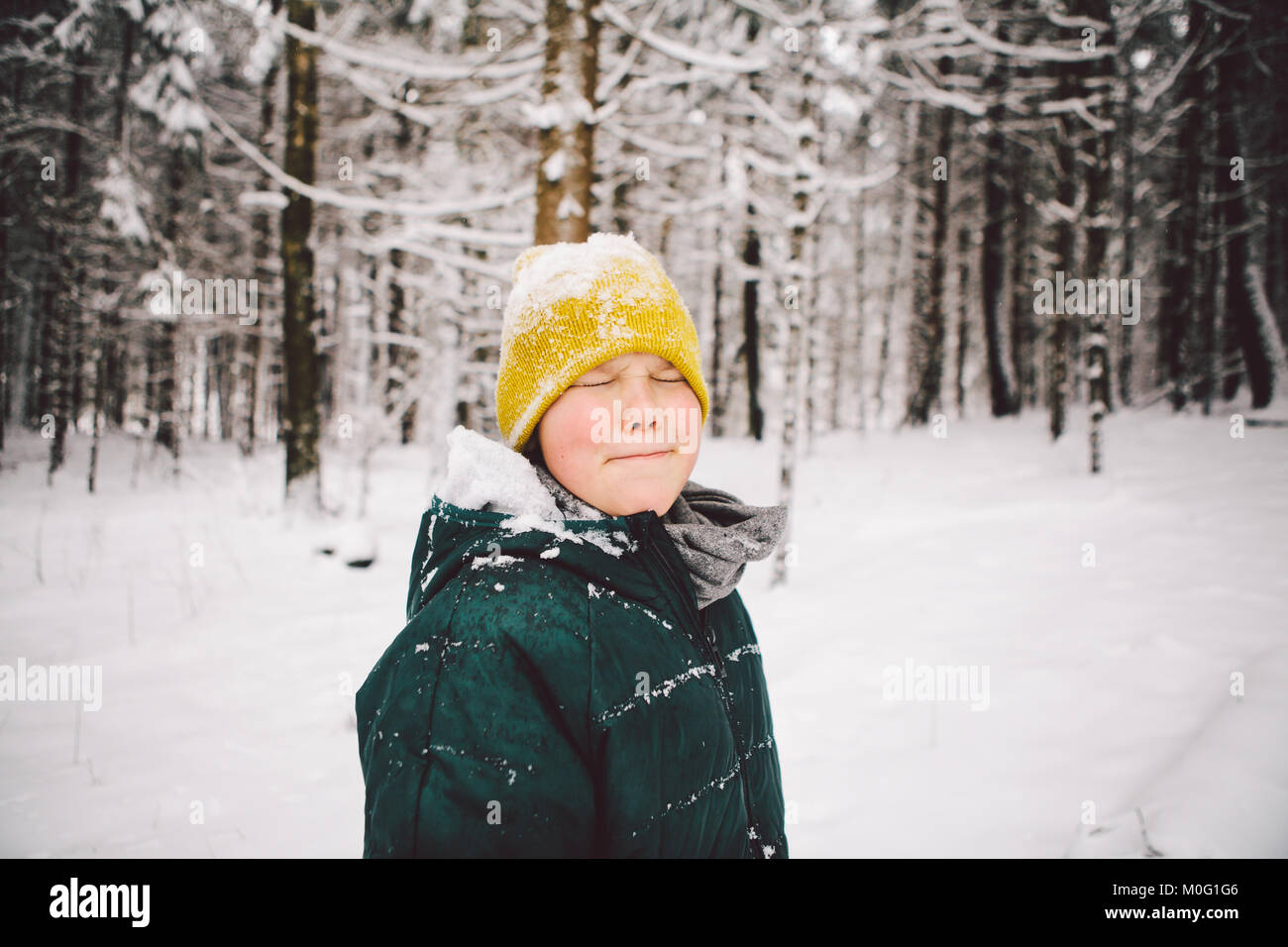 A teenage boy in winter clothes is standing and posing in snowy winter forest. - Stock Image