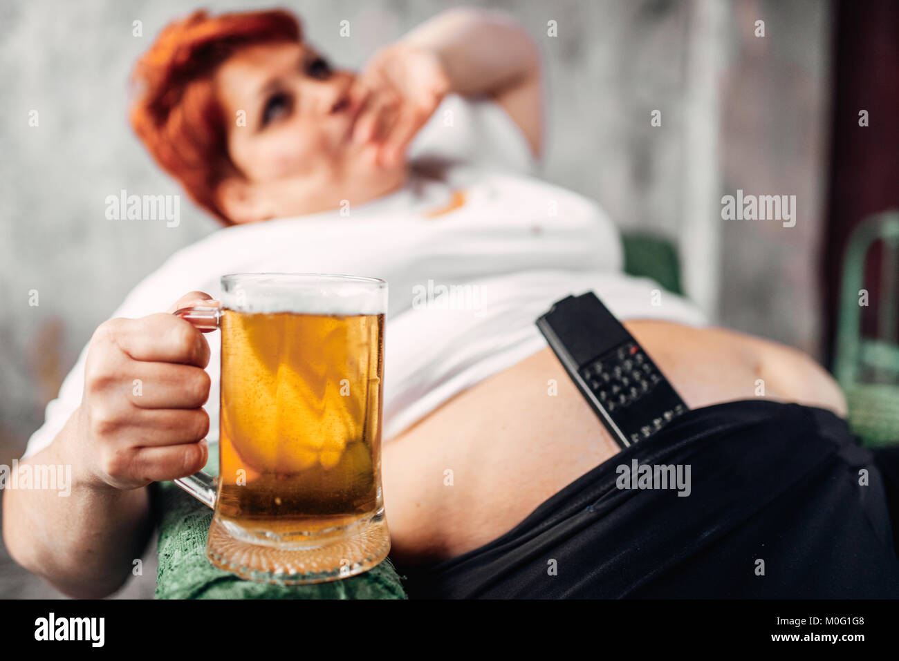 Overweight woman with glass of beer in hand, obesity. Unhealthy lifestyle, fatty female - Stock Image