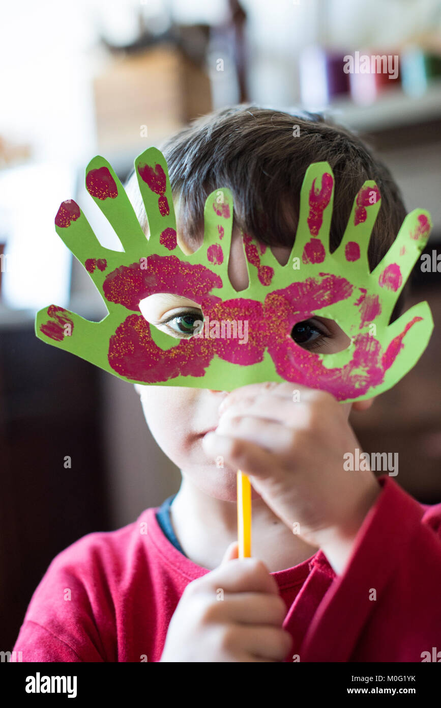 portrait of a 6 year old boy with a carnival mask made by himself at home Stock Photo