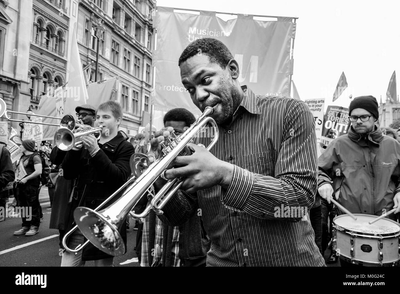 London black and white street photography: Members of the Musicians' Union perform along route of anti-austerity - Stock Image