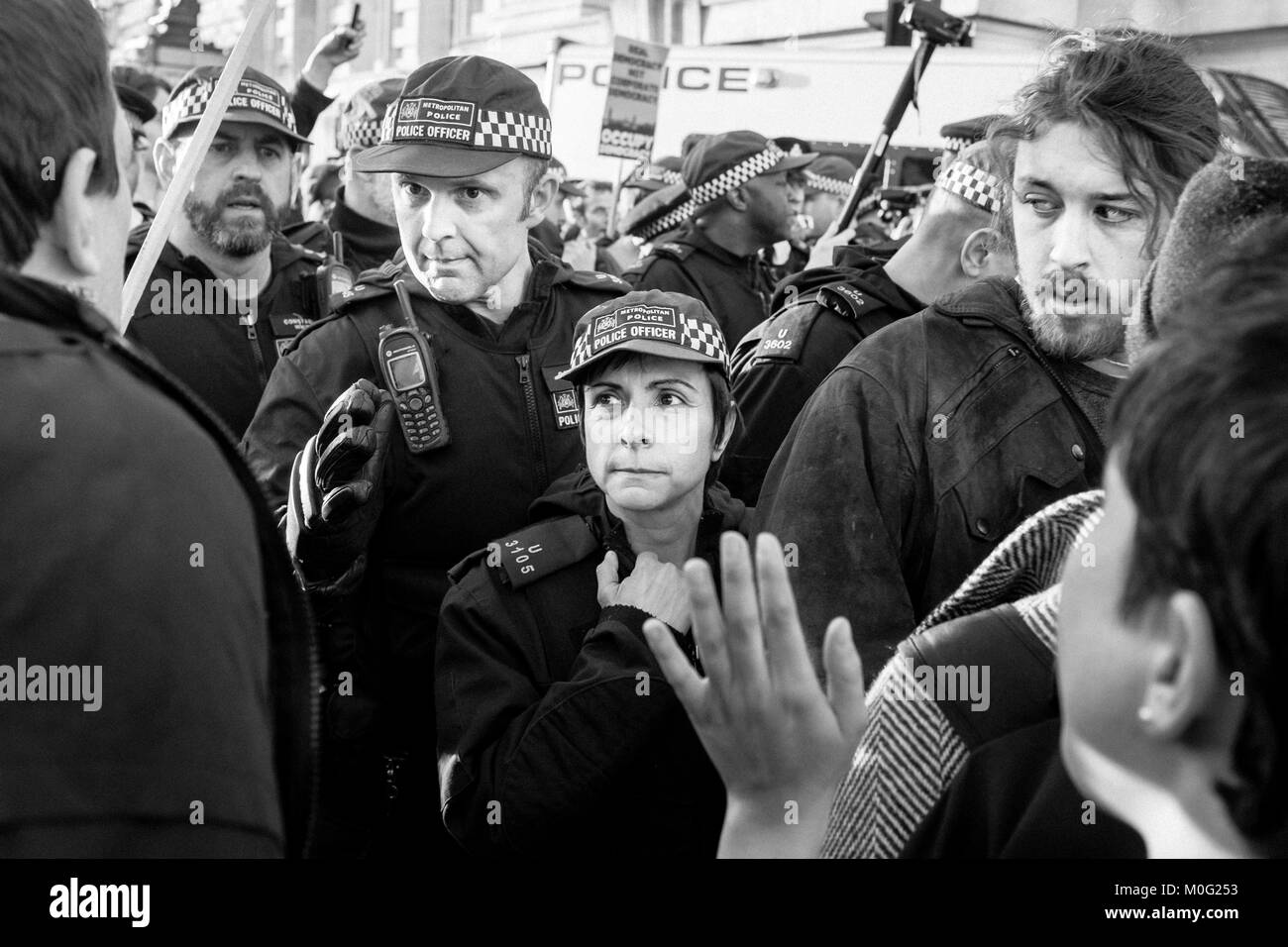 London Black and white street photography: Metropolitan Police Officers confront demonstrators during protest march - Stock Image