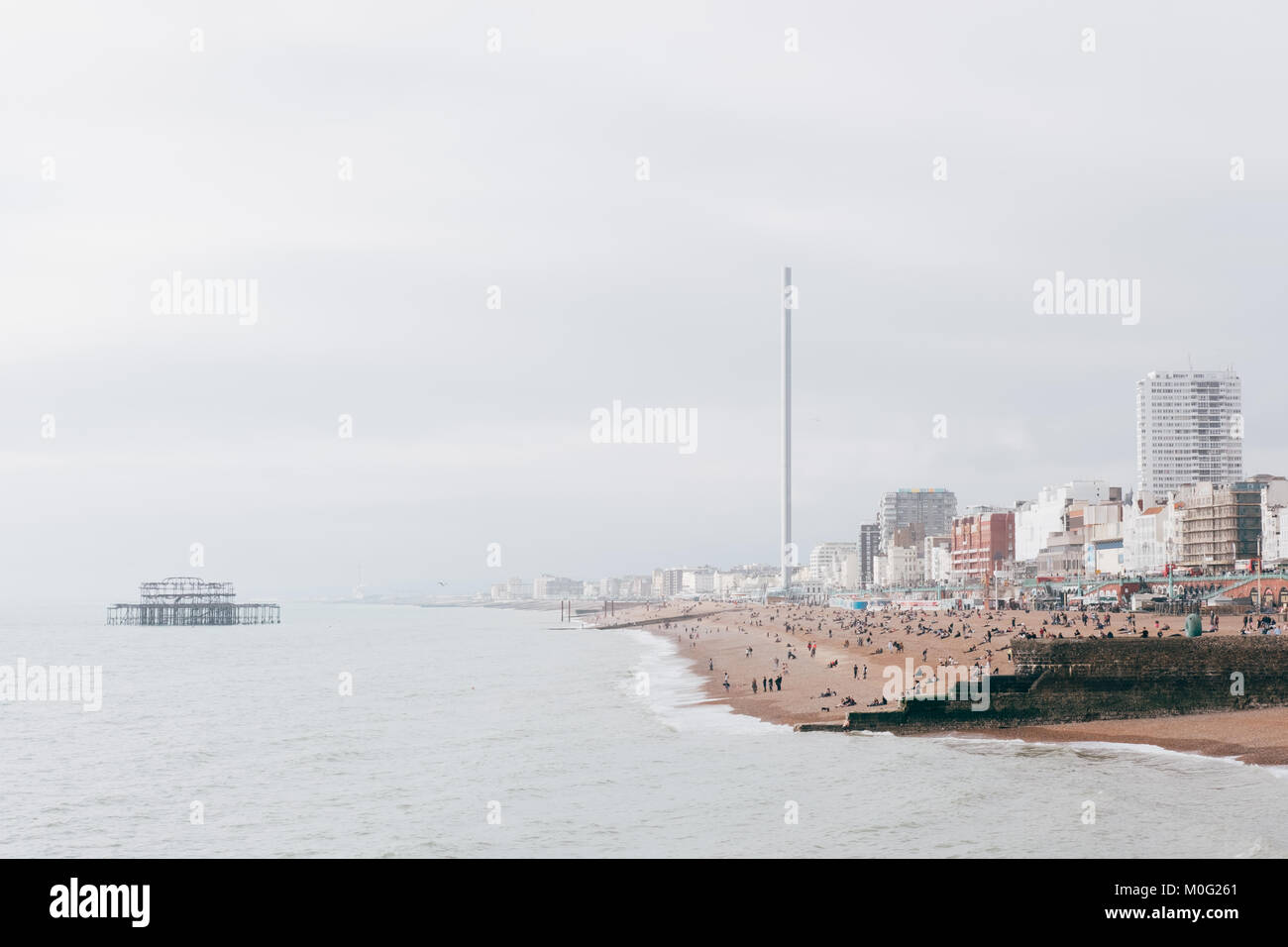 People on the beach and West Pier at Brighton, the most popular seaside destination in the UK for overseas tourists. - Stock Image