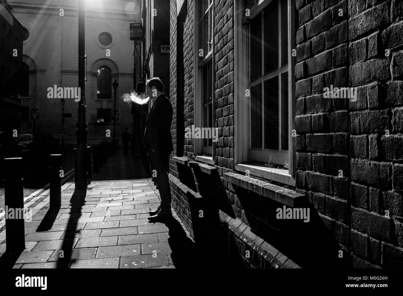 London Black and white street photography: Man smoking in street. - Stock Image