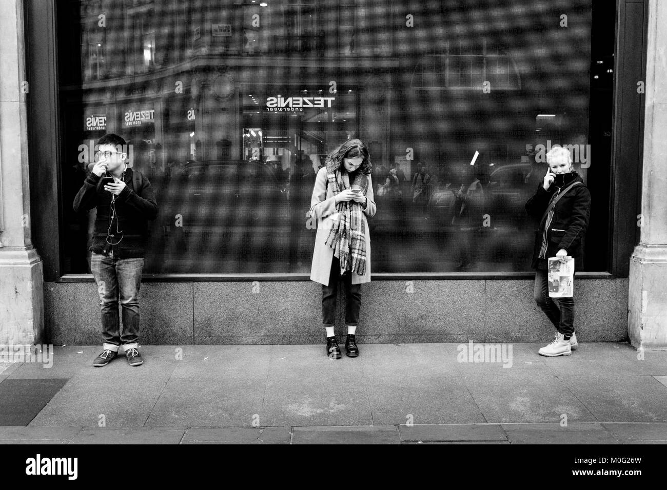 London Black and white street photography: three young people using mobile phones in street - Stock Image